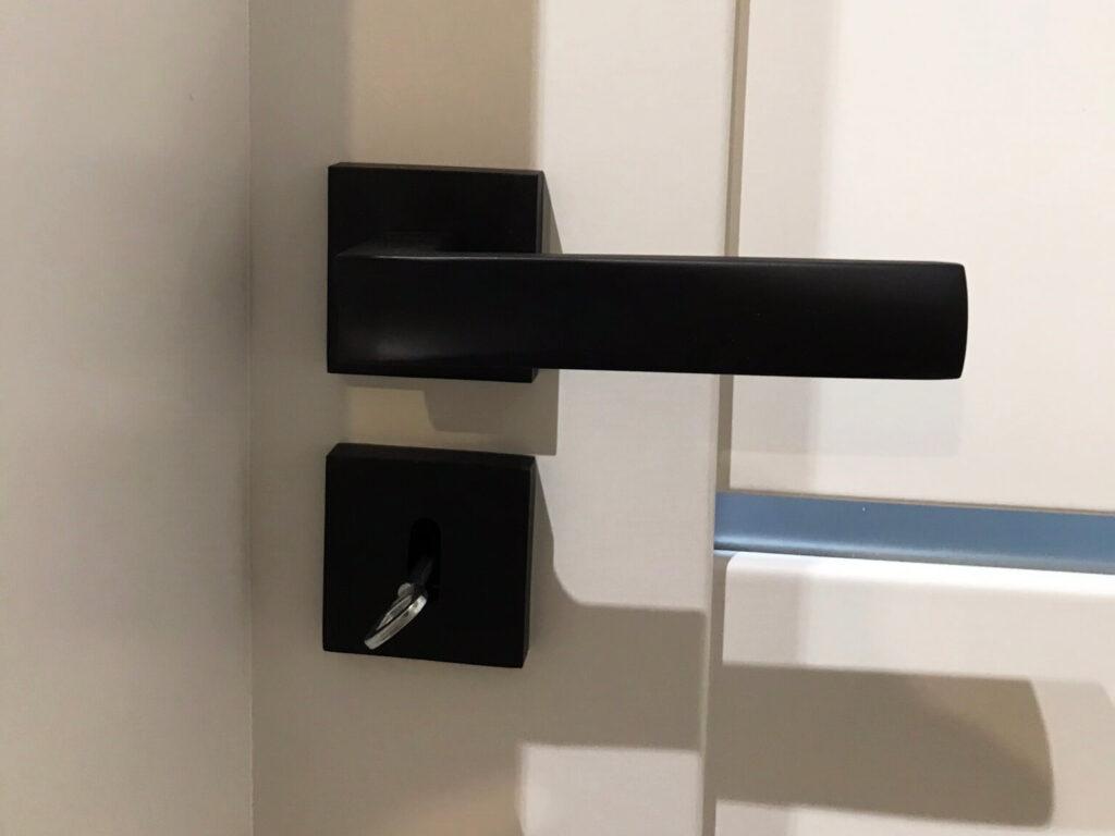Białe drzwi z czarnymi klamkami